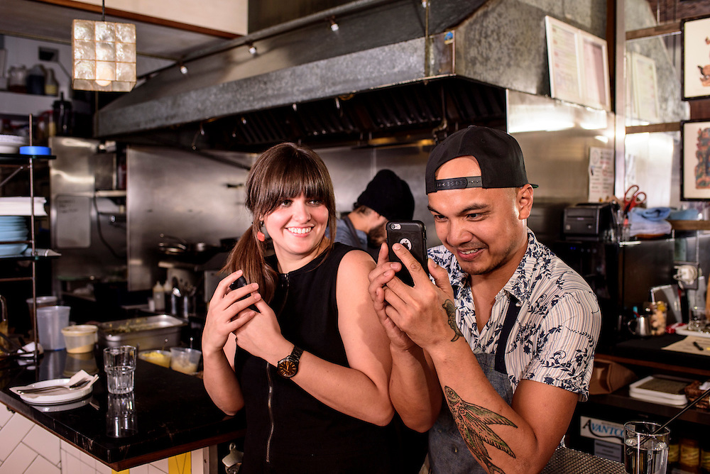 """Washington, D.C. - November 19, 2016: An impromptu photo shoot unfolds moments before Bad Saint opens Friday evening. Front of house employee Stephanie Impala and head chef Tom Cunanan take pictures of Amanda Carpenter one of their co-workers who's in """"nice light.""""<br /> <br /> D.C. Filipino restaurant Bad Saint was recently named the second best new restaurant in America by Bon Appetite.<br /> <br /> <br /> CREDIT: Matt Roth for The New York Times<br /> Assignment ID: 30199012A"""