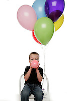 Tucker Ward 5 year old birthday boy photo in studio celebrating by blowing up balloons with air.
