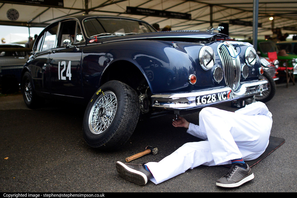 © Licensed to London News Pictures. 13/09/2013. Chichester, UK A mechanic repairs a car. People enjoy the atmosphere at the 2013 Goodwood Revival. The event recreates the glorious days of motor racing and participants are encouraged to dress in period dress. The revival is the only event of its kind to be staged entirely in the nostalgic time capsule of the 1940s, 50s and 60s Photo credit : Stephen Simpson/LNP.