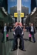 A symmetrical gentleman wearing a pinstripe suit talks on his phone, reflected in plate glass in the City of London, the capitals financial district also known as the Square Mile, on 6th April 2017, in London, England.