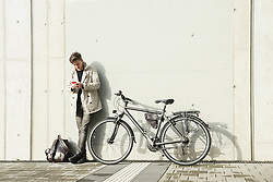 Young man text messaging on mobile phone and leaning against concrete wall, Munich, Bavaria, Germany