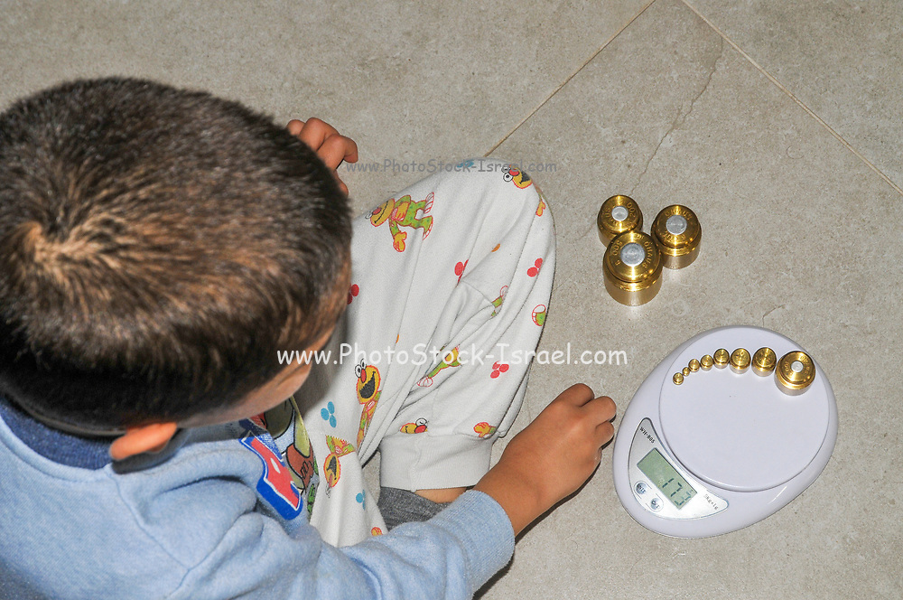 Young boy of 5 is practising arithmetic with the aid of precision weights and a digital scale