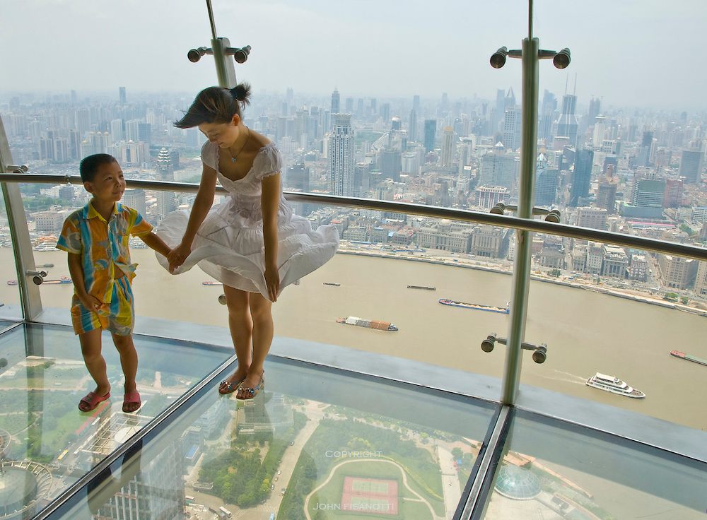 A sister and brother on the lower floor observation deck of the Oriental Pearl Tower overlooking  Shanghai and the Huangpu River