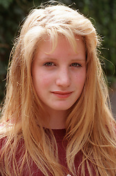 Portrait of teenage girl with long blond hair smiling,