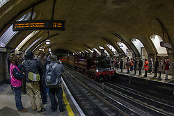 © Licensed to London News Pictures. 13/01/2013, London, UK. People watch the newly restored Met Locomotive No. 1 steam train pass Baker Street underground station in London, Sunday, Jan. 13, 2013, to mark the 150th anniversary of the opening of the world's first underground in January 1863. Linked to the Met Locomotive No 1 engine was the oldest surviving operational underground carriage, the Metropolitan Railway Jubilee Carriage 353, a set of four Chesham carriages and the world's oldest electric locomotives in service, No 12 Sarah Siddons. Photo credit : Sang Tan/LNP