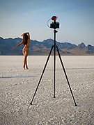 Nude woman posing in front of a camera on a tripod on the Bonneville Salt Flats, Utah