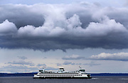Storm-cloud formations hover over a Washington State Ferry in Elliott Bay in this view from West Seattle. (Ken Lambert/The Seattle Times)