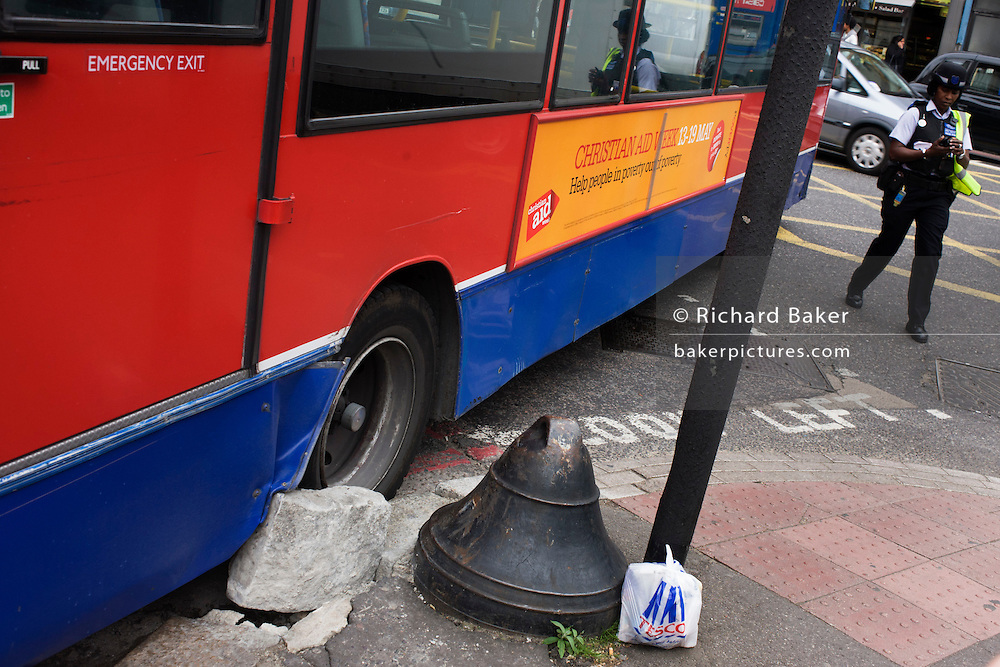 A London bus in the aftermath of striking a kerb stone in a King's Cross street corner.