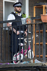 © Licensed to London News Pictures. 01/07/2020. London, UK. A child's bicycle can be seen as a police officer guards a block of flats in Monarch Parade in Mitcham, south London after a four year old girl was found seriously injured yesterday. She was taken to hospital where she later died. A woman, aged 35, is fighting for her life after she was also found suffering serious injuries inside the property. Photo credit: Peter Macdiarmid/LNP