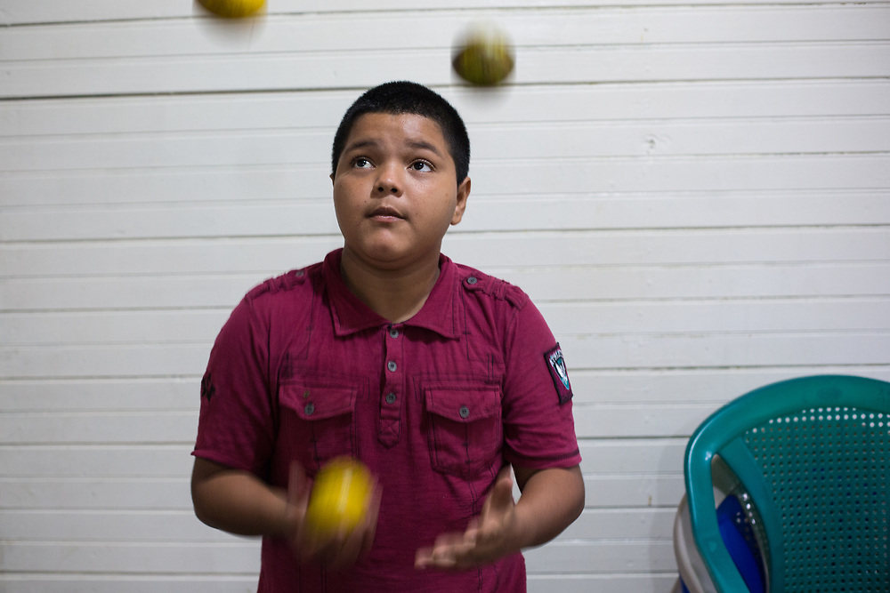 """Mario David Castellanos Murillo,12, """"the Caravan Boy"""". <br /> <br /> Mario's mother has a long-term mental illness, his father works long hours as a security guard and doesn't earn the minimum salary. Mario had been spending his time in the street instead of going to school, juggling for tips or selling chewing gum at traffic lights in San Pedro Sula. When the caravan left in October last year, Mario decided to join it. Mario's case was highlighted in some media who dubbed him The Caravan Boy.<br /> <br /> """"It's dangerous in the street, there are lots of kids in the street, some people take drugs, they smoke glue, sometimes kids disappear. So. I went on the caravan, on my own. I went walking sometimes, sometimes I jumped on lorries, trailers, sometimes I got lifts in little cars. At the border I went through running, with everyone else that was running, everyone was running. They caught me in Mexico, they were using the crying gas and a woman grabbed me and pulled me away, she took me to a clinic. Then they took my details, and took me to a children's home and flew me back to Honduras on an aeroplane. That was sort of okay. It was easy to escape from the place they put me. I got over the wall, I was in the mountains running. I hid in a tree for a while. Then I got back here, I'm living with my uncle [guardian]"""". <br /> <br /> Mario's guardian says that Mario's case highlights the precarious social reality of many people living in families with very low incomes, or with mental health issues. He spoke at length about problems of poverty around the city of San Pedro Sula, the industrial capital of Honduras. If people are lucky, they have a job, but they work long hours and can't make ends meet. People have a right to escape terrible conditions if they can see a better alternative somewhere else, he says. Through CASM, he says, Mario has been able to start going to school."""