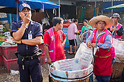 """26 SEPTEMBER 2012 - BANGKOK, THAILAND: A police officer and porters at a corner in Khlong Toey Market in Bangkok. Khlong Toey (also called Khlong Toei) Market is one of the largest """"wet markets"""" in Thailand. The market is located in the midst of one of Bangkok's largest slum areas and close to the city's original deep water port. Thousands of people live in the neighboring slum area. Thousands more shop in the sprawling market for fresh fruits and vegetables as well meat, fish and poultry.     PHOTO BY JACK KURTZ"""