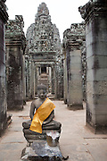 A stone statue of Buddha with a yellow tunic material draped over his shoulder in a walkway leading to the Bayon Temple in the ancient Angkor Thom, Siem Reap Province, Cambodia, South East Asia.  (photo by Andrew Aitchison / In pictures via Getty Images)