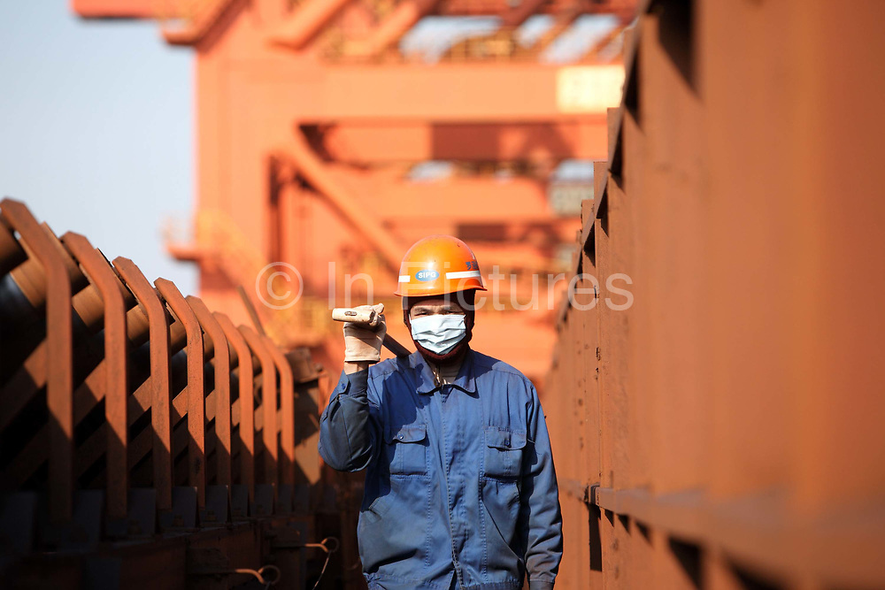 A dock worker walks by a conveyer belt at an iron-ore transfer and storage center operated by the Shanghai International Port Group in Shanghai, China on 26 January 2010. China's economic boom and hunger for natural resources has been a blessing for countries such as Australia and Brazil, who controls most the world's high quality iron ore deposits.