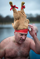 © Licensed to London News Pictures. 25/12/2017. London, UK. A competitor wearing. Turkey hat after the race as members of the Serpentine Swimming Club brave the cold waters at the Serpentine Lake in Hyde Park, London to compete for the traditional Peter Pan Cup on Christmas Day, December 25, 2017. Photo credit: Ben Cawthra/LNP