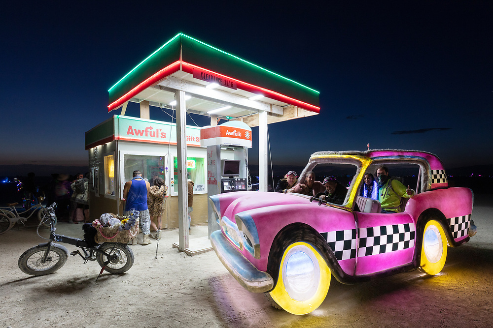 """Hani's Deep Playa Tax Refueling at Awful's Gas & Snack<br /> by: Matthew Gerring & Crank Factory<br /> from: San Francisco, CA<br /> year: 2019<br /> <br /> Awful's Gas & Snack: Your Gateway to the Big Wild! See one of the few remaining gasoline stations, painstakingly preserved since the mid-21st century. Travel back to a time when hardy men roamed the """"open road"""" seeking fortune & freedom. Wilderness passes & provisions available. NO GAS AVAILABLE FOR PURCHASE, PLEASE DON'T ASK.<br /> <br /> URL: http://awfulsgas.com<br /> Contact: awfuls@awfulsgas.com<br /> <br /> https://burningman.org/event/brc/2019-art-installations/?yyyy=&artType=H#a2I0V000001AVwVUAW"""