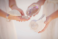 The hands of two women with seashells.