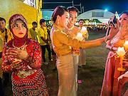 "05 DECEMBER 2014 - BANGKOK, THAILAND: Thai women take a ""selfie"" while they hold lit candles for the King's Birthday on Sanam Luang in Bangkok. Thais marked the 87th birthday of Bhumibol Adulyadej, the King of Thailand,  Friday. The King was born on December 5, 1927, in Cambridge, Massachusetts. The family was in the United States because his father, Prince Mahidol, was studying Public Health at Harvard University. He has reigned since 1946 and is the world's currently reigning longest serving monarch and the longest serving monarch in Thai history. Bhumibol, who is in poor health, is revered by the Thai people. His birthday is a national holiday and is also celebrated as Father's Day. He is currently hospitalized in Siriraj Hospital, recovering from a series of health setbacks.     PHOTO BY JACK KURTZ"