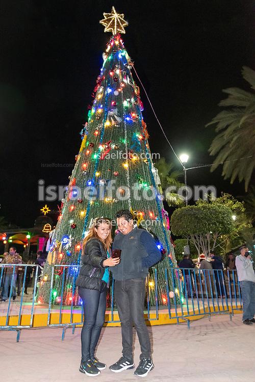 03 de diciembre de 2020. Tultepec, Estado de México. Evento de encendido de luces del árbol navideño de la plaza principal de este municipio. Una pareja se fotografía con el árbol como fondo.