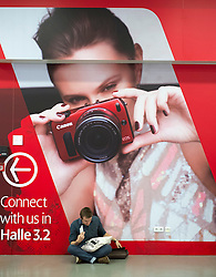Visitor sitting in front of large poster advertising new Canon camera on second day of bi-annual Photokina photography and imaging trade fair held in Cologne Germany; Wednesday September 2012