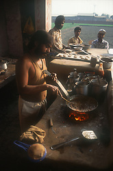 Road side café in India with man cooking,