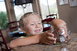 Boy putting savings in glass jar (Credit Image: © Image Source/Dan Bannister/Image Source/ZUMAPRESS.com)