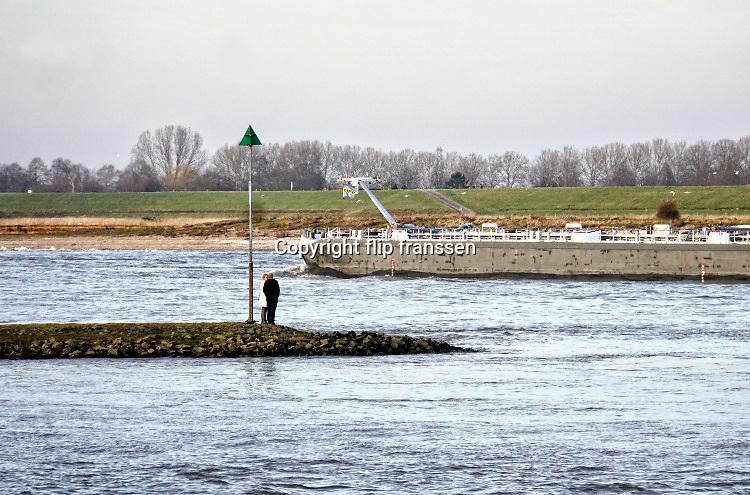 Nederland, Ooij, 17-2-2019Twee mensen staan op een krib in de rivier de Waal, rijn . Over het water vaart een binnenvaartschip, een tanker, tankschip . Man en vrouw .Foto: Flip Franssen