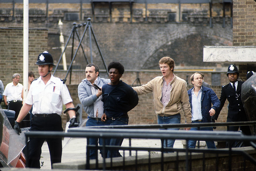 Police arrest local men in the aftermath of the Brixton Riots, South London,UK in April 1981. metropolitan plain clothes officers take a suspect away. Photographed by Terry Fincher