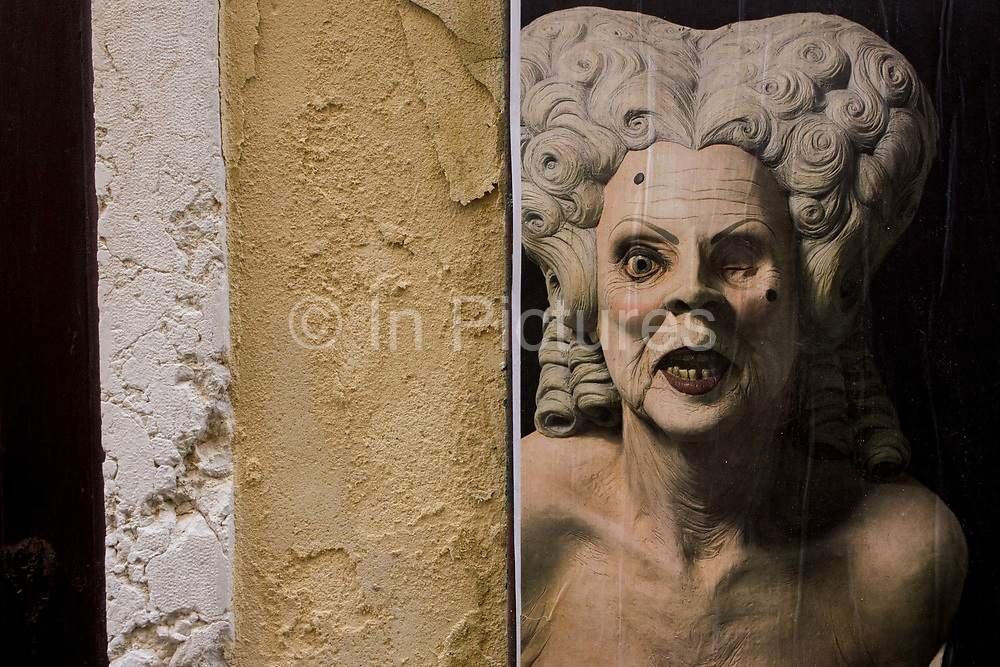 The texture of wall plaster echoed in the skin of a theatrical character in the San Marco shopping district of Venice, Italy. The unknown character appearing in a part during July 2015 is a disturbing, ugly old hag of a woman with bad teeth and an empty eye socket. Her loose skin is pallid and is echoed in the taut, crumbling nature of the plaster render.