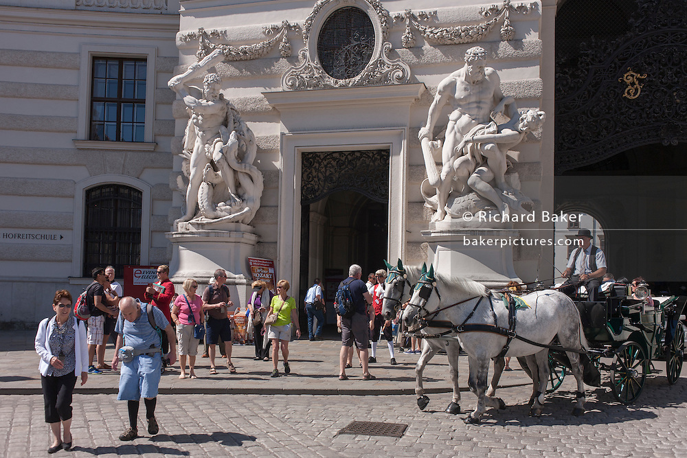Dominated by giant Romanesque figures depicting Hercules slaying Hydra, elderly tourists and a fiaker (horse-drawn carriage) vie for cobbled space outside St. Michael's Church on Michaelerplatz, on 28th June 2016 in Vienna, Austria. St. Michael's is one of the oldest churches in Vienna. (Photo by Richard Baker / In Pictures via Getty Images)