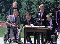 United States President George H. W. Bush signs the Americans with Disabilities Act of 1990 into law during a ceremony on the South Lawn of the White House in Washington, D.C. on July 26, 1990. Pictured (left to right): Evan J. Kemp, Jr., Chairman, U.S. Equal Employment Opportunity Commission; Reverend Harold Wilke; President Bush; Sandra Parrino; and Justin Dart. The act prohibited employer discrimination on the basis of disability. Credit: Ron Sachs / CNP /ABACAPRESS.COM