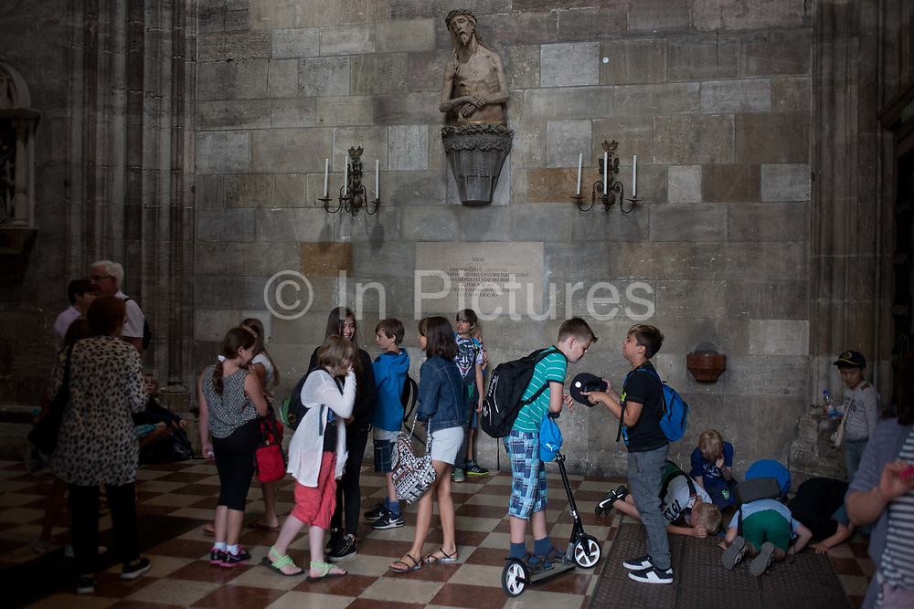 An accompanied group of Austrian schoolchildren mess about below an effigy of Christ in St. Stephens Church on 28th June 2016, in Vienna, Austria. While some chat among themselves, others are on their knees to inspect below the floor through the gaps of a grating. St. Stephens Cathedral is the mother church of the Roman Catholic Archdiocese of Vienna and stands on the ruins of two earlier churches, the first a parish church consecrated in 1147. The most important religious building in Vienna, St. Stephens Cathedral has borne witness to many important events in Habsburg and Austrian history.