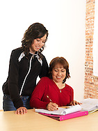 Hispanic girl (14 years old) and mother at desk with school work.