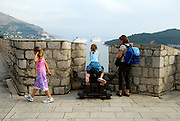 Mother and two children (9 years old, 5 years old), one sitting on cannon, looking through city wall parapet to cruise ships in distance. Dubrovnik old town, Croatia