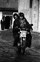 Two Tibetan nomads riding a motorcycle through Langmusi, China.