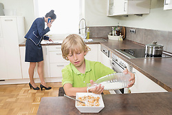 Boy pouring milk in muesli while mother has business call in kitchen, Bavaria, Germany
