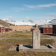 The main square of Pyramiden. A bust of Lenin watches over the ruined settlement and the Nordenskioldbreen Glacier beyond.