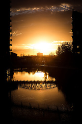 © Licensed to London News Pictures . 21/11/2013 . Manchester , UK . A fiery orange sunset over the River Irwell on the border between the two cities of Salford and Manchester , this evening ( Thursday 21st November 2013 ) as a commuter crosses a pedestrian footbridge from Salford to Manchester . Photo credit : Joel Goodman/LNP