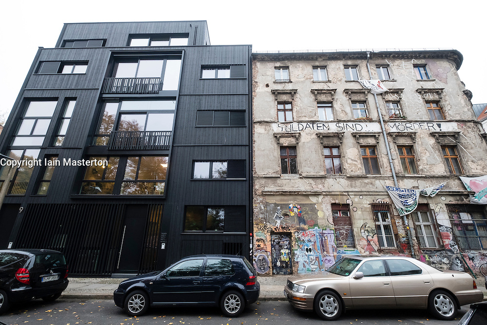 Contrast between modern office building and old apartment building used as a squat in Mitte Berlin Germany