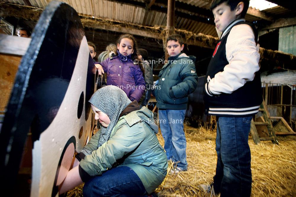 Nederland, Den Ilp , 12 april 2010..Kinderen van een z.g. zwarte school (school met kinderen van ouders van allochtone afkomst) uit Amsterdam West leren bij melkveehouderij Het Elenlenveld uit Ilpendam wat het is om in een agrarisch bedrijf te werken..Vele van deze kinderen hebben geen idee hoe het er aan toe gaat in een agrarisch bedrijf..Op de foto melkt een moslima meisje  op een houten koe wat het is om een koe te melken...Foto:Jean-Pierre Jans