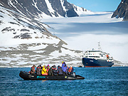 Tourists travel on the liveaboard M/V Plancius and Oceanwide Expeditions to experience the beauty of the Arctic.
