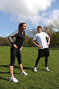 A woman with her personal trainer, exercising in a park in London, UK. Fitness, exercise and wellbeing has never been more popular in the United Kingdom as people strive to live healthy lives.