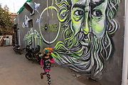 A child dressed in a colourful wig from a nearby village runs past graffiti in Champa Gali, New Delhi, India. Champa Gali is the latest and most intimate of Delhis urban creative villages.