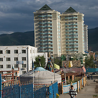 A traditional nomadic ger contrasts with modern high-rise buildings in Ulaanbaator, Mongolia
