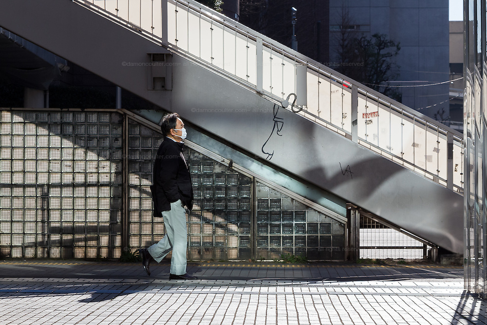 A Japanese man walks by a foot bridge which is graffitied with a face.  Shibuya, Tokyo, Japan. Friday January 13th 2017