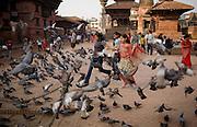 Teenage Nepali girls run through a flock of pigeons in Durban Square on May 12, 2008, in Kathmandu, Nepal (David Stubbs / Aurora)