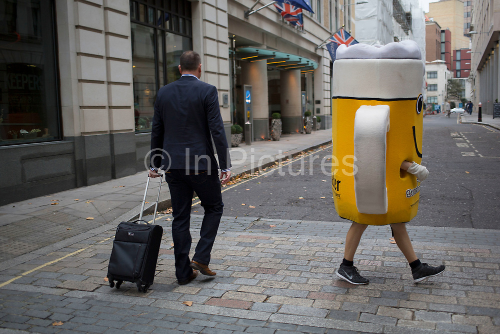 A man dressed up as a glass of beer in the City of London, UK. Weird street scene as a man in a suit passees this large scale glass of lager on it's way to a promotional event.