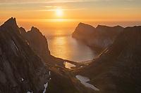 June midnight sun hangs low over sea above Kvalvika beach, Lofotodden national park, Moskenesøy, Lofoten Islands, Norway