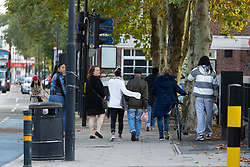 Supporters help the victim's father, Cecil Tomlin, 84, away from the scene following the murder on October 17th of Ian Tomlin, 46, at the Doddington Estate in Battersea, South London . Battersea, London, October 18 2018.