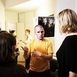 "SAINT-OUEN, FRANCE. SEPTEMBER 2, 2011. Photographer Remi Chapeaublanc explaining his work at the people who came. ""Les Expos a la Maison"" (Home Exhibitions) is a one-night exhibit organized at a private individual's home. Photo: Antoine Doyen"