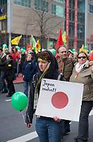 """DEU, Deutschland, Germany, Berlin, 26.03.2011:<br />Demonstration für den Ausstieg aus der Atomkraft unter dem Motto """"ausgestrahlt - gemeinsam gegen Atomenergie"""". Eine Demonstrantin mit einem Pappschild der japanischen Flagge und der Aufschrift """"Japan mahnt"""" auf der Potsdamer Strasse."""